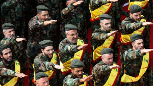 Members of Lebanon's Shiite Hezbollah movement salute behind the coffins of three comrades killed in combat in Syria during their funeral in the southern Lebanese city of Nabatieh on November 8, 2017. / AFP PHOTO / Mahmoud ZAYYAT (Photo credit should read MAHMOUD ZAYYAT/AFP/Getty Images)